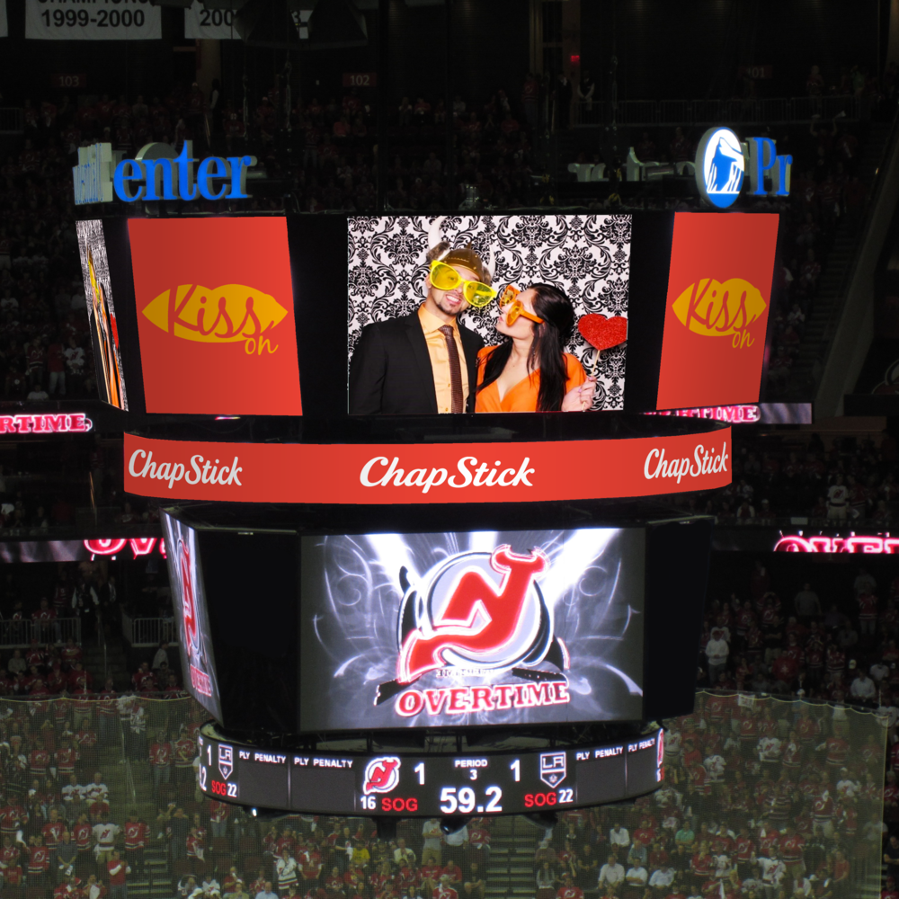 The Jumbotron takes digital copies of the photos taken in the Photo Booth and projects them during the Kiss Cam moments.