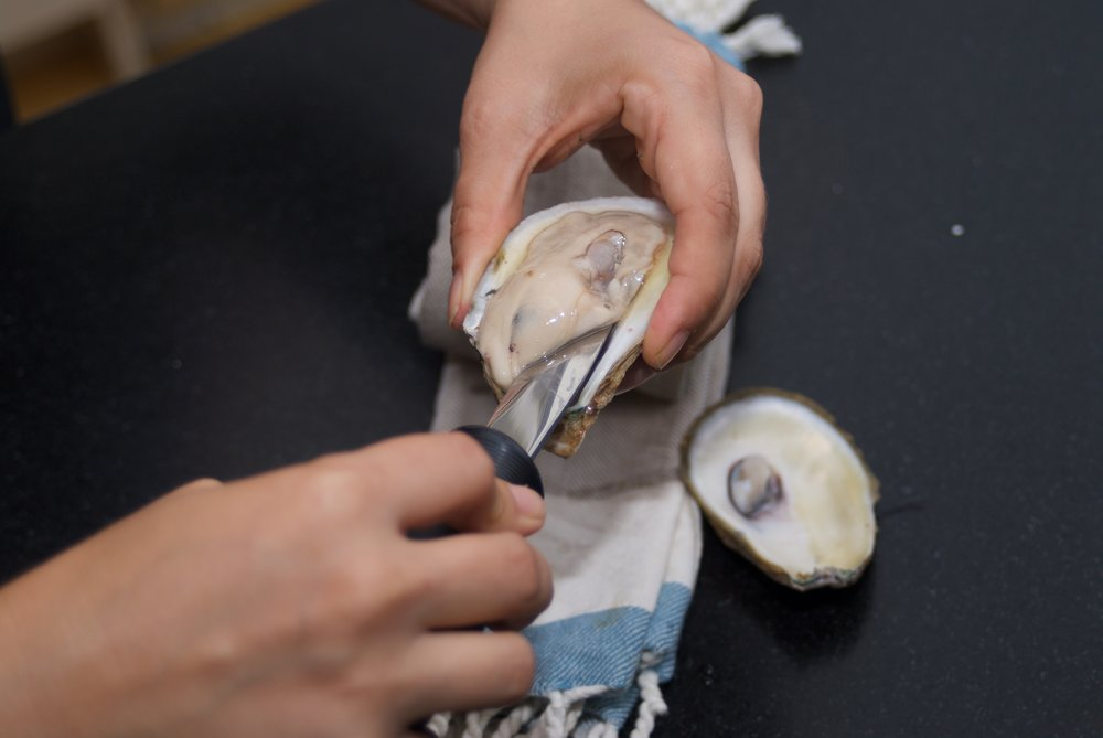 Slide the knife underneath to separate the oyster from it's shell. Do your best to not cut into the oyster - it's just neater.