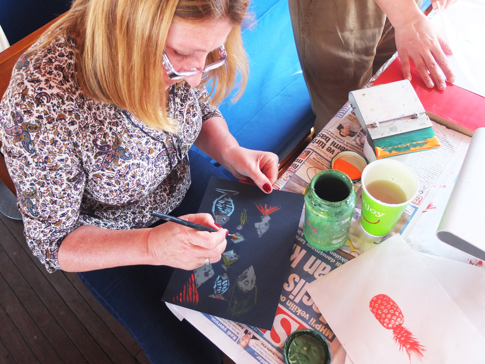 Karen adding hand-painted touches to stencilled fish.