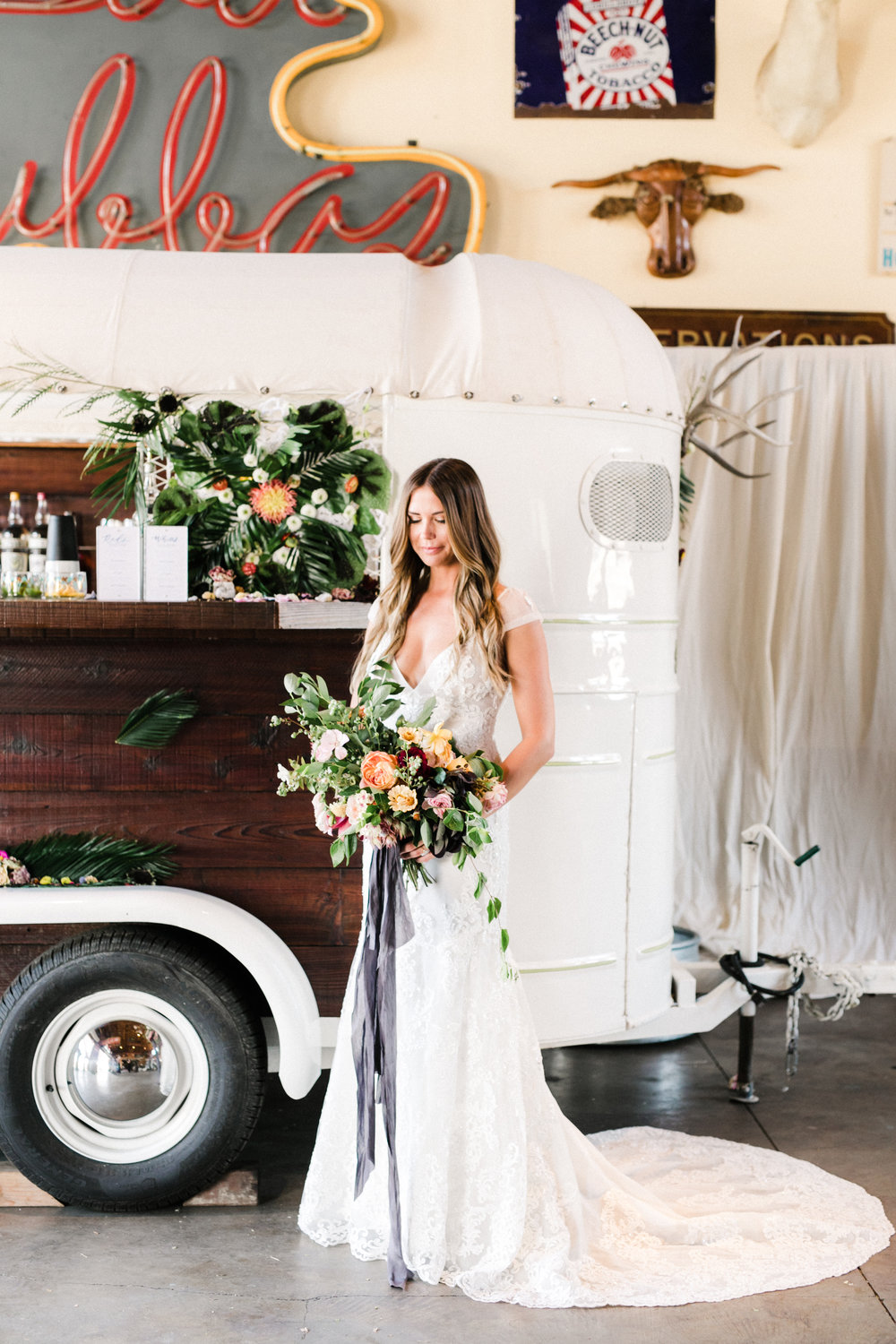 A beautiful shot of this boho, indie, bride in front of Tinker Tin Trailer Co.'s vintage horse trailer bar.