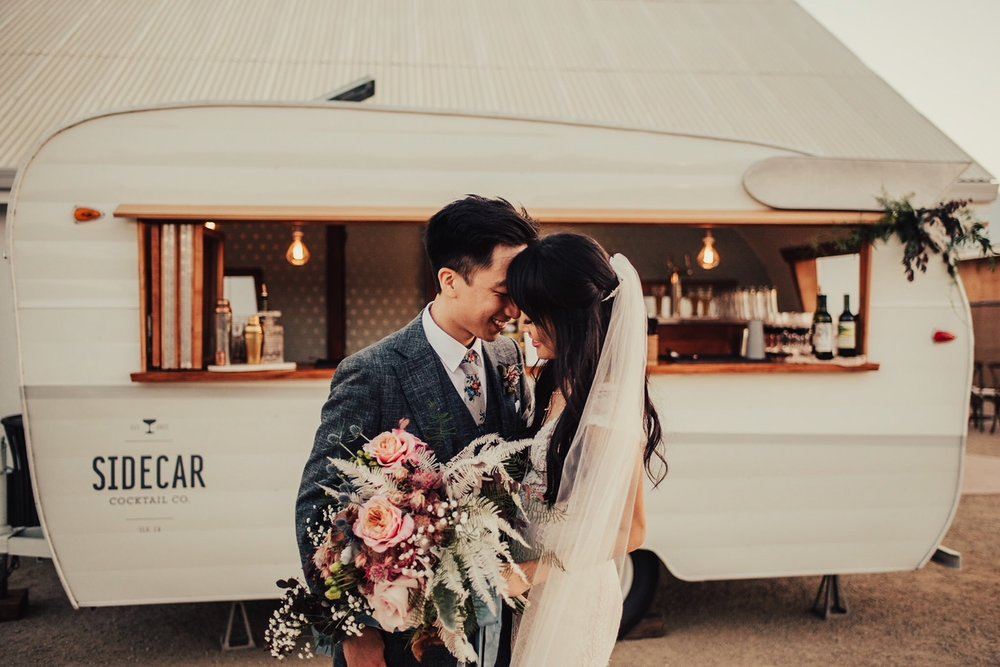 A quiet and romantic moment captured in front of Tinker Tin Trailer Co.'s vintage mobile bar trailer between a bride and groom at The White Barn in San Luis Obispo, California.