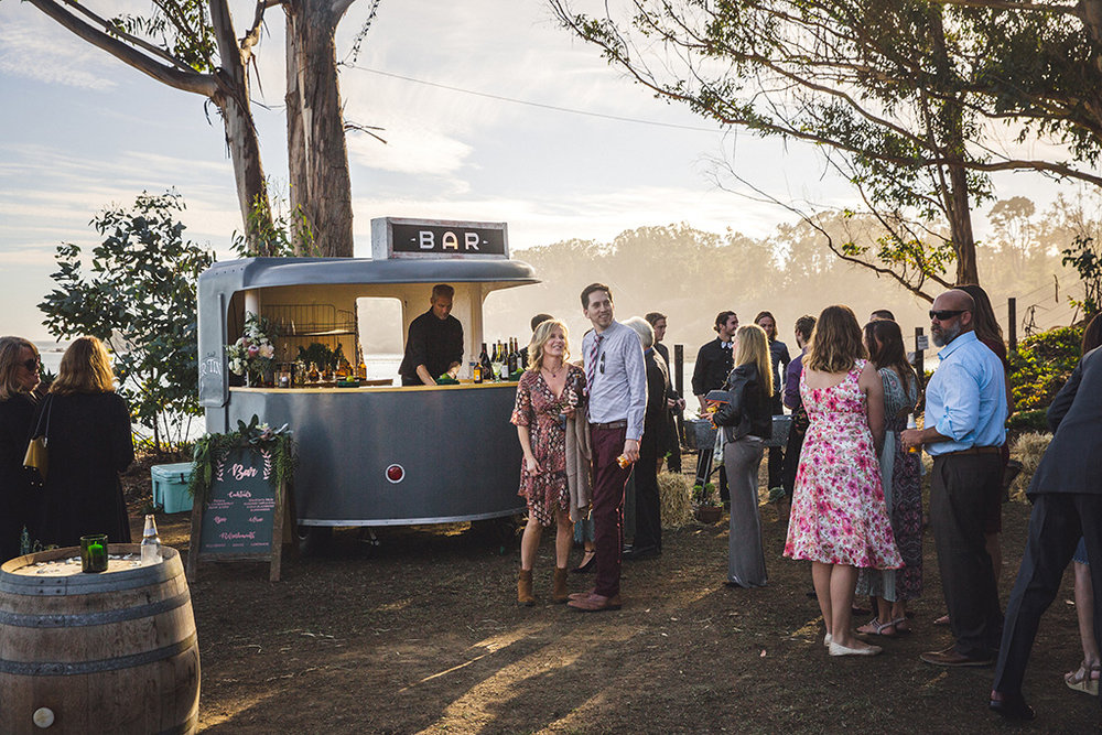 Serving cocktails out of our 1958 roll-o-vend vending bar trailer at gorgeous Hearst Ranch wedding with an ocean view.