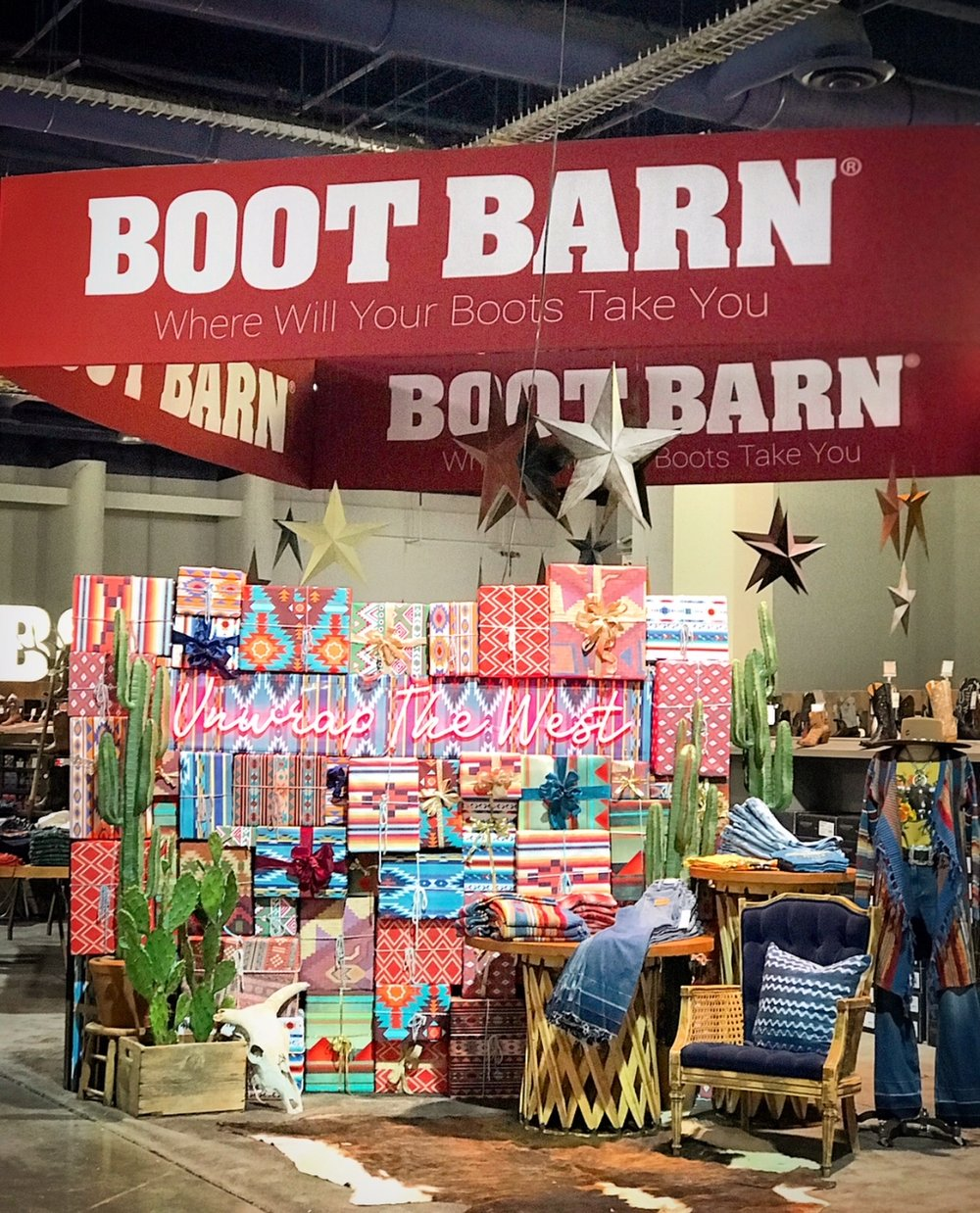 Custom built Modern - Southwestern step and repeat wall with presents, neon sign and cactuses for an expo center build out at the National Finals Rodeo Cowboy Christmas