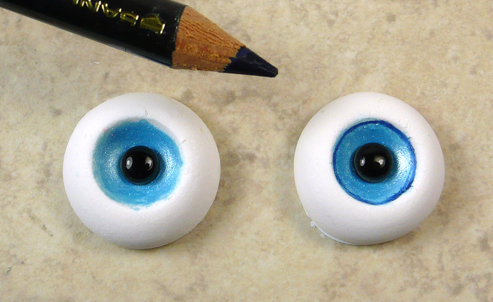 7. Once the eyes have baked and cooled, you can outline the iris with a darker colored pencil. Here I am using a dark blue.