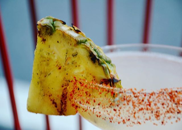 "ANNABELLE ""This is our take on a classic margarita (tequila, triple sec, lime) enhanced with pineapple juice and anise (Absinthe) flavor notes. The grilled pineapple and tajin rim adds a bit of a kick to the cocktail."""