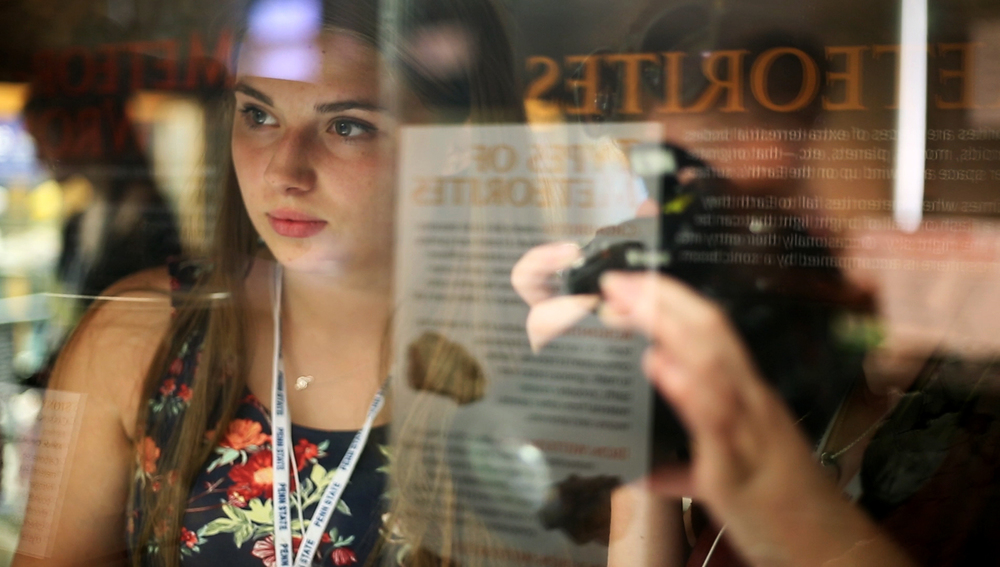 Linden Markley, a camper of Penn State's Multimedia Journalism camp, looked through a display at the Earth and Mineral Sciences Museum.