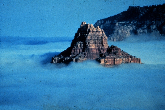 A rocky peak rises from a sea of fog in an Arizona Valley; image by NOAA.