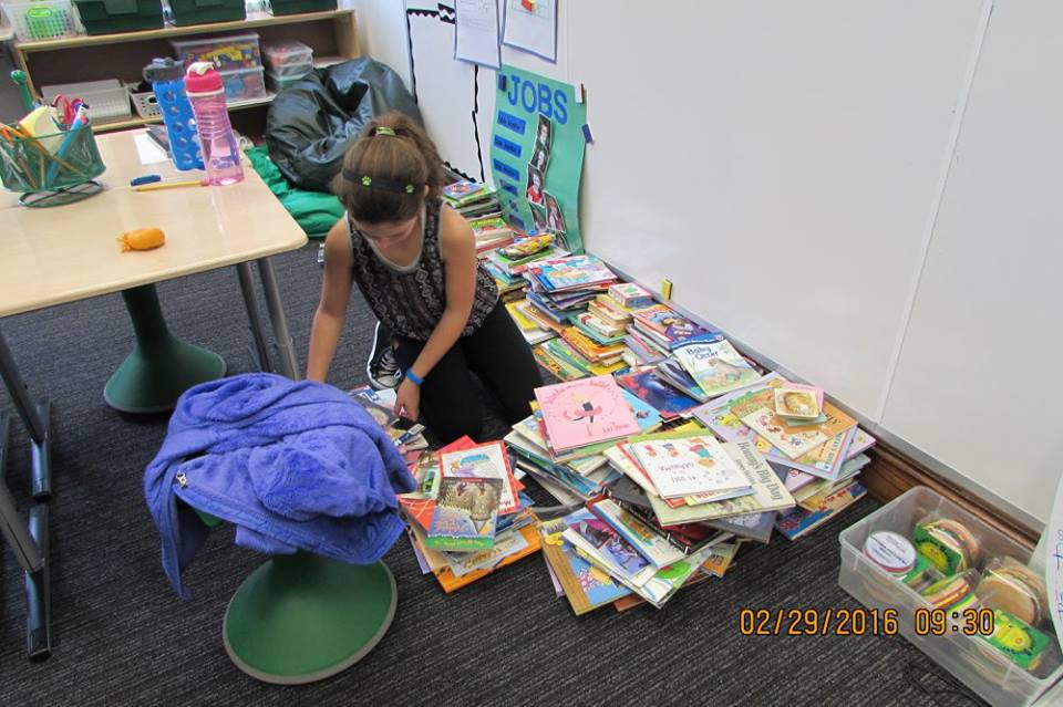 Fourth graders at Alexandria Country Day School organizing the books they collected for our library projects.