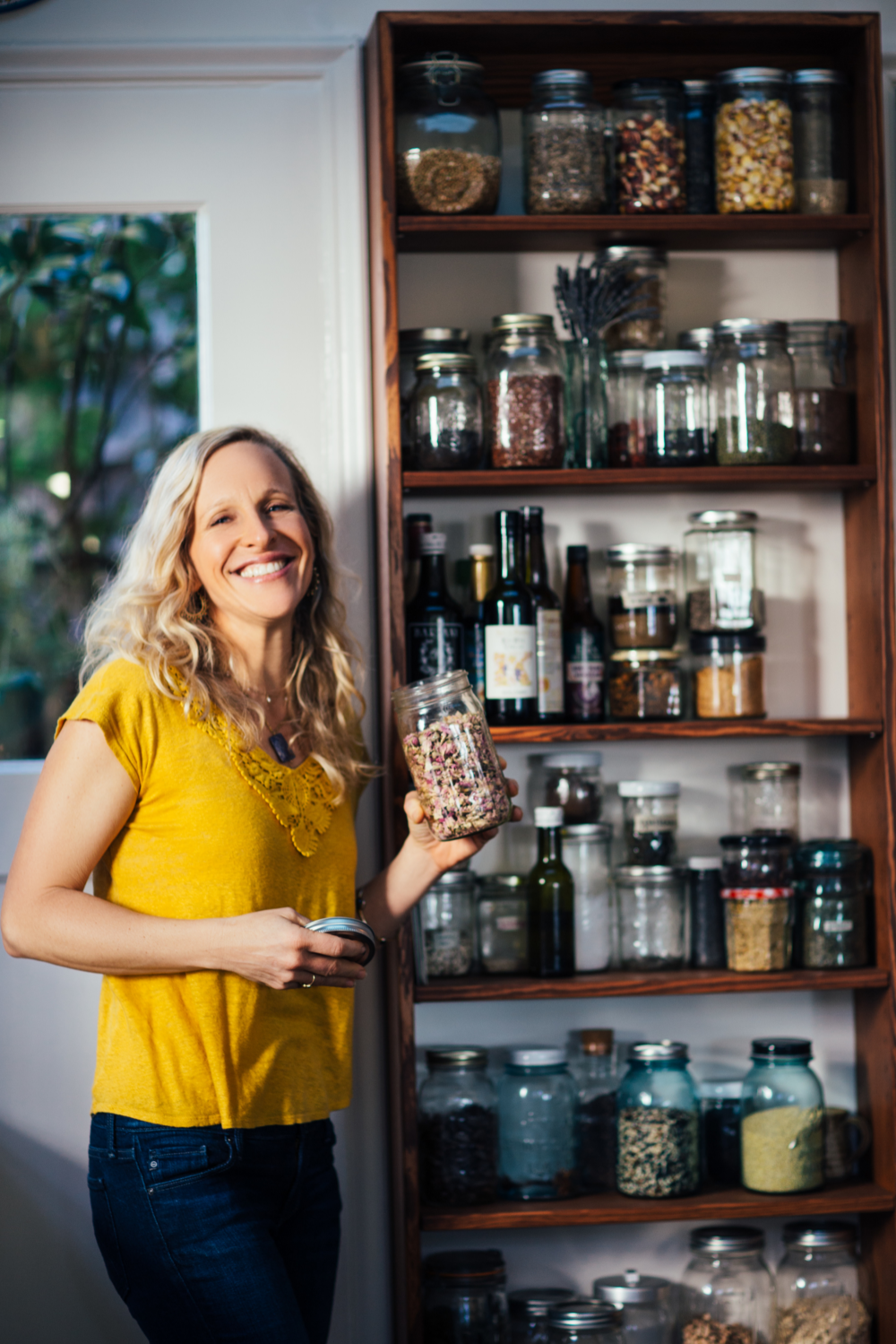 Dara with many jars of herbs, spices, and teas