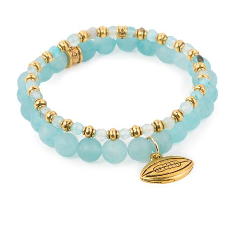 "Catch the Spirit  (Set of Two)  Blue agate and dyed jade bracelet set of two with gold-detail and football charm. Measures approximately 7.5"" in length. With the purchase of this bracelet set, 25% of gross profit goes to Water.org.   All bracelet sets come with a pouch and a hang-tag detailing the mission of each charity."