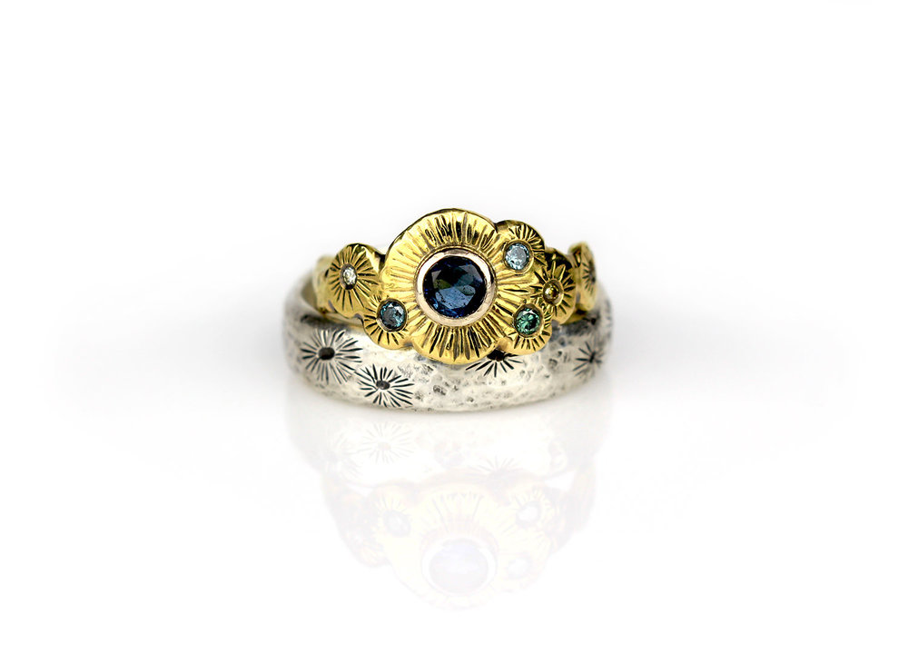Christa & Bennett's custom wedding rings:  Christa's ring features a Maine-mined blue tourmaline encased in a white gold bezel on a 18k yellow gold ring with a hand-chased barnacle-inspired texture, encrusted with tiny blue and champagne diamonds. Bennett's wide band ring complements Christa's with the same hand-chased barnacle texture in argentium silver.