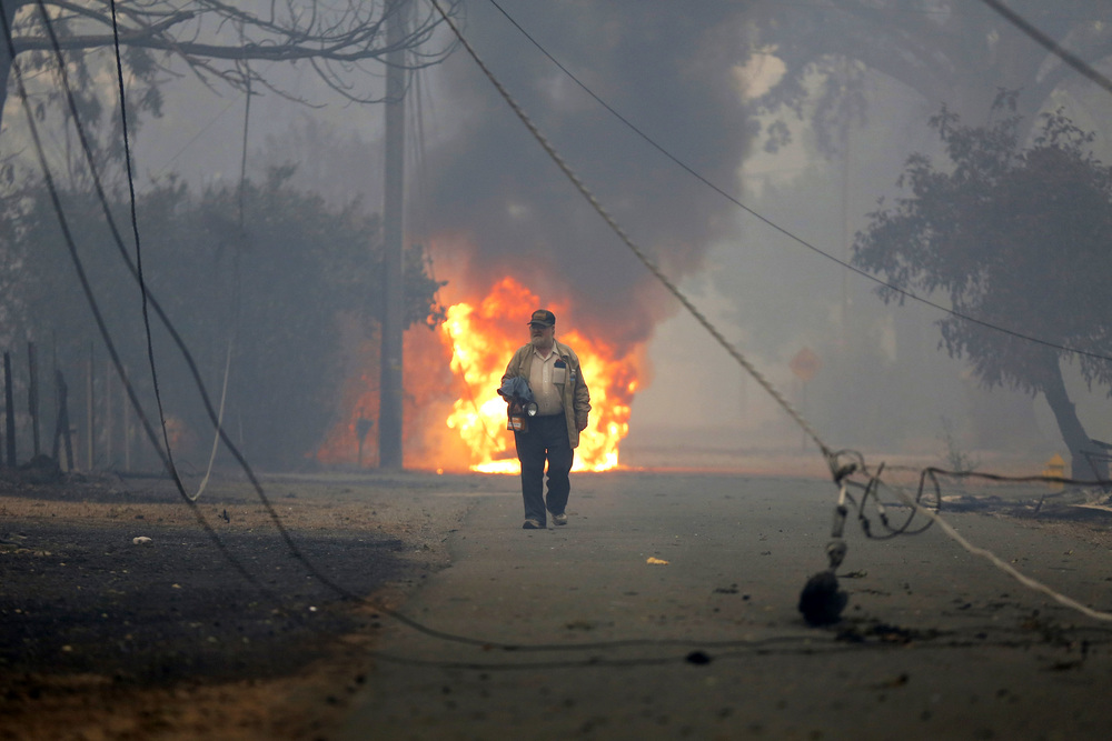 Orval Young walks toward what remains of his property as a truck burns behind him in Middletown, California, on Sunday, Sept. 13, 2015.