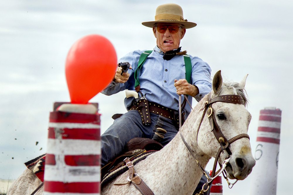 Jim Rogers aims at a target balloon during a competition at Ben Avery Shooting Range in Phoenix, Arizona, on Thursday, Feb. 27, 2014.