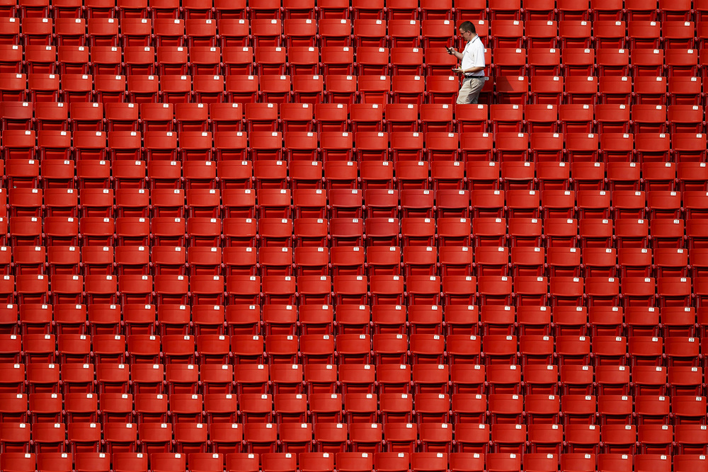 A Washington Redskins employee walks through the stands before a preseason game against the New England Patriots at FedExField on Thursday, Aug. 7, 2014.