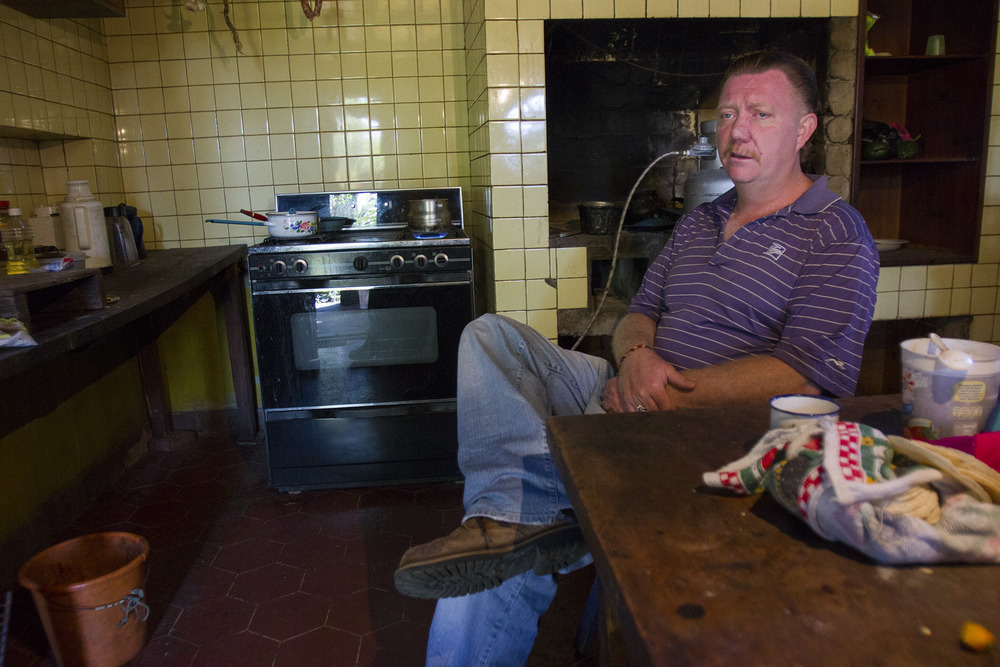 Virgil Edwards waits for his breakfast of coffee and black beans to cook while sitting in one of the few rooms still standing on his property after the invasion several years prior.
