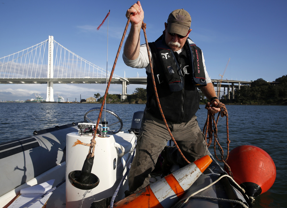Ian McClelland lifts the anchor of a sailboat racing mark to throw in the waters of Clipper Cove off Treasure Island, California, on Thursday, May 5, 2016.