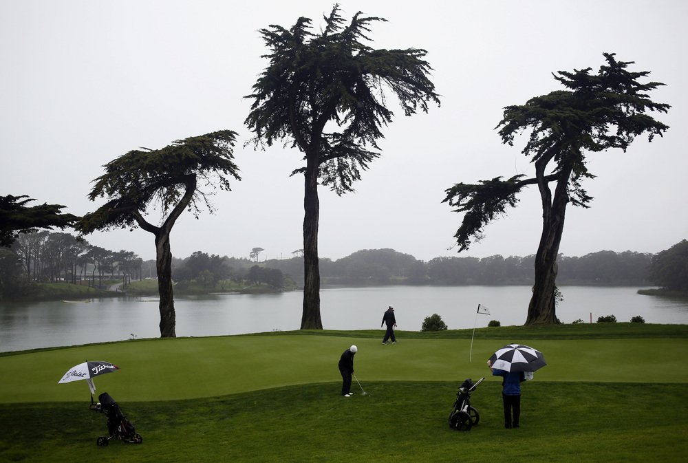 Daniel Connolly (center) lines up a shot during the San Francisco City Golf Championship at Harding Park in San Francisco, California, on Sunday, March 13, 2016.