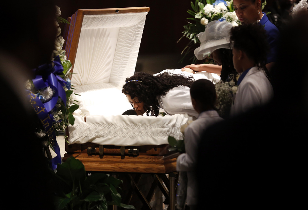 Audrey Hughes Cornish kisses her son Torian Hughes during his funeral at Shiloh Church in Oakland, California, on Monday, Jan. 11, 2016.