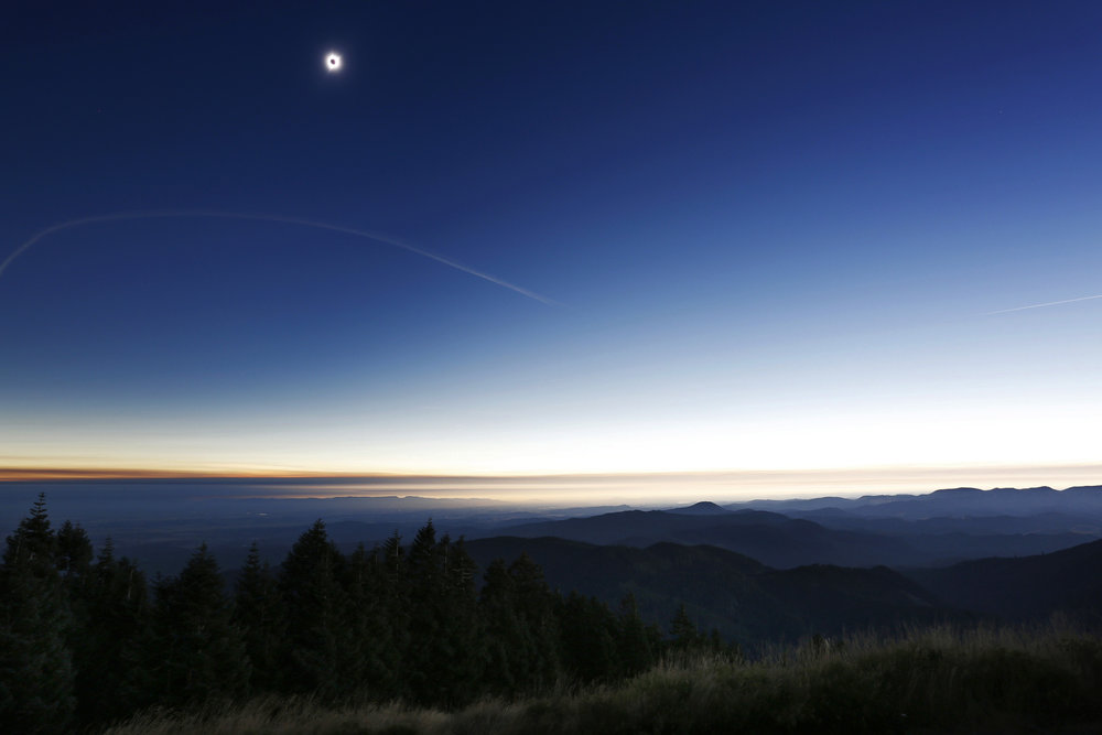 The total solar eclipse reaches totality over a landscape scene from the top of Marys Peak in the Siuslaw National Forest on Monday, Aug. 21, 2017.