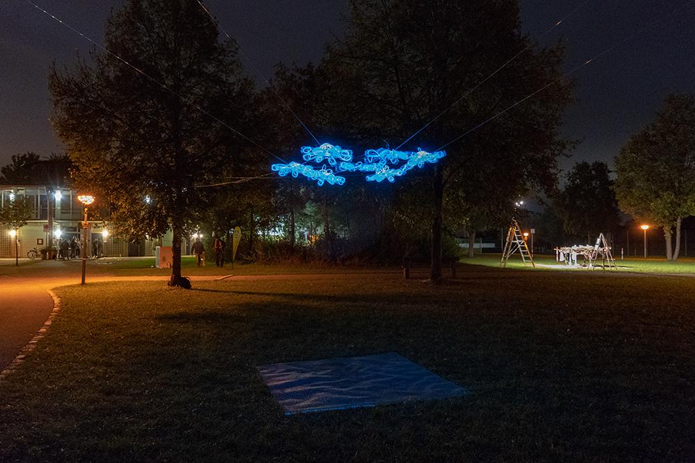 Installation Vergissdeinnicht , September 2018  7 Lichtobjekte geformt aus Plastikflaschen und angeordnet in Form einer Vegissmeinnichtblume, aufgebaut in etwa 2,2 Meter Höhe auf einer Wiese zwischen Bäumen (2 x 2 Meter), klare Folie, Ton