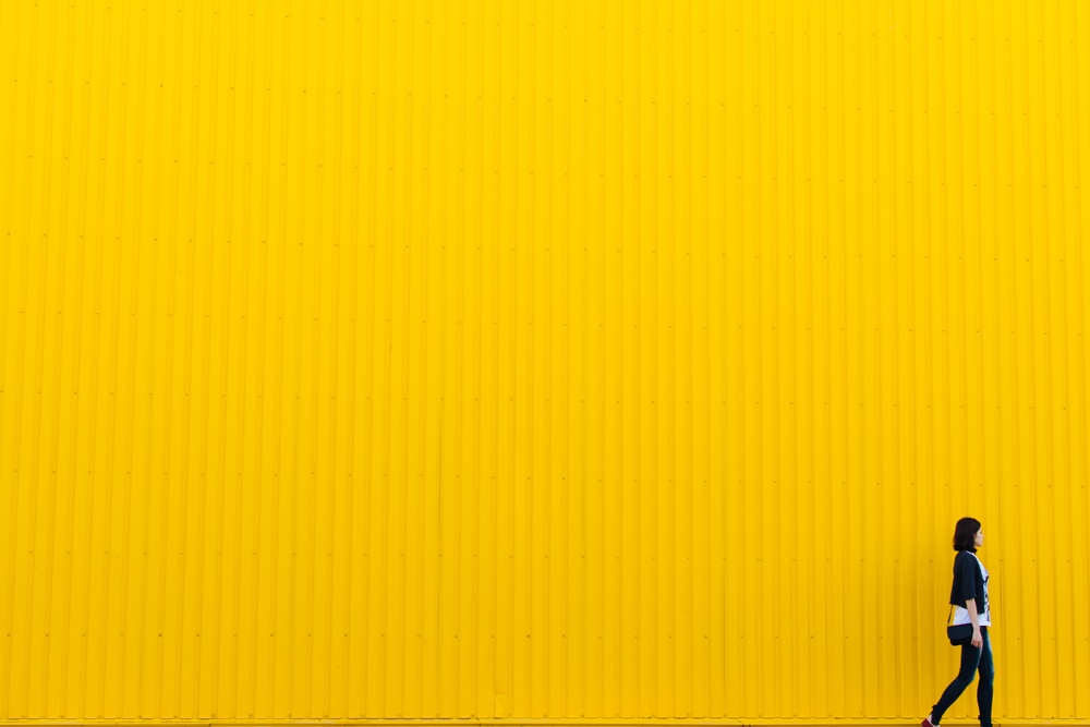woman walking yellow background