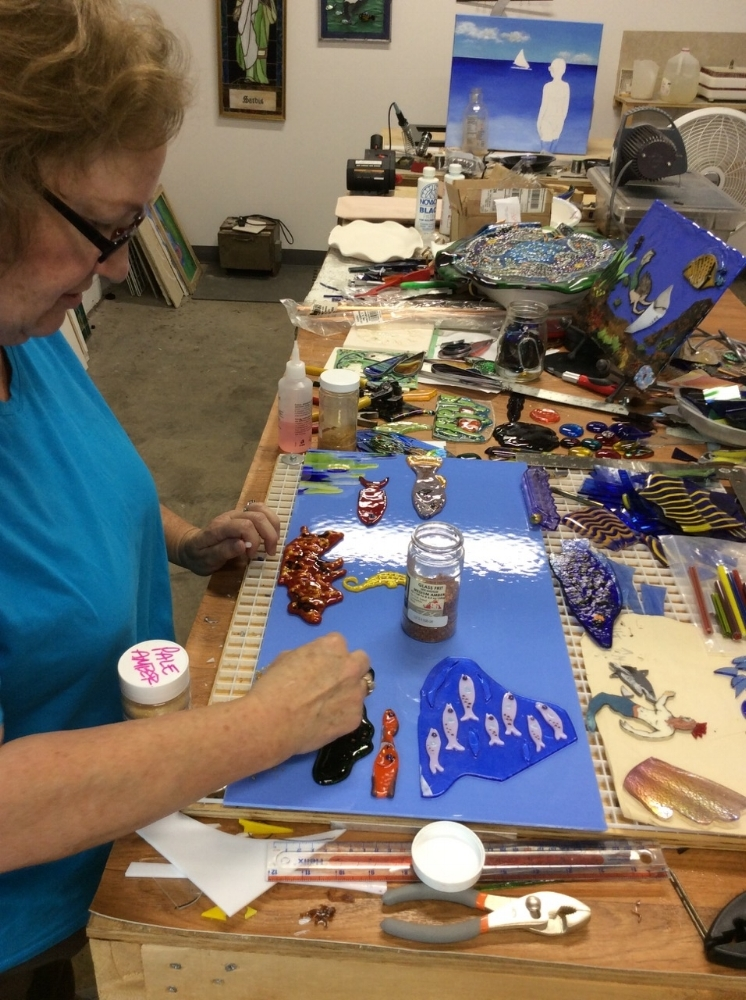 Mary Jane CApron setting up afused - glass artwork in her studio at ClearWater artist studios.