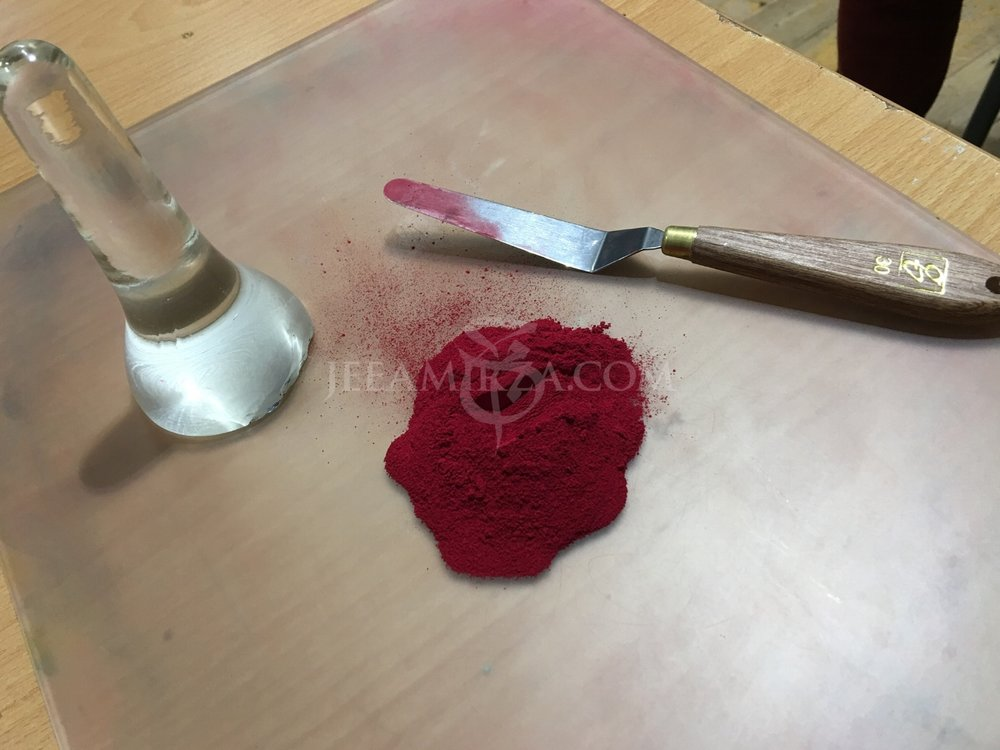 Alizarin Crimson pigment shown next to a glass muller and palette knife