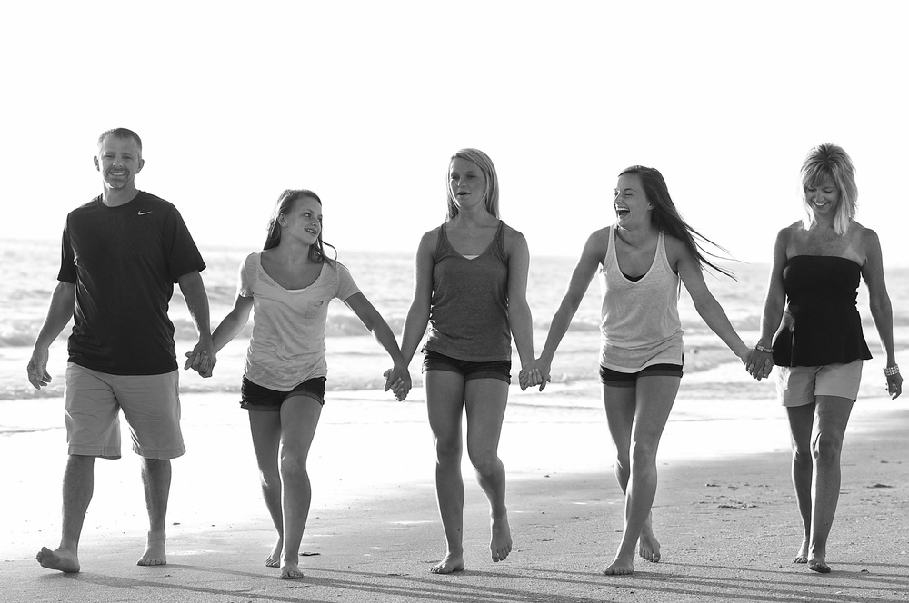 family-walking-down-florida-beach-portrait-candid.jpg