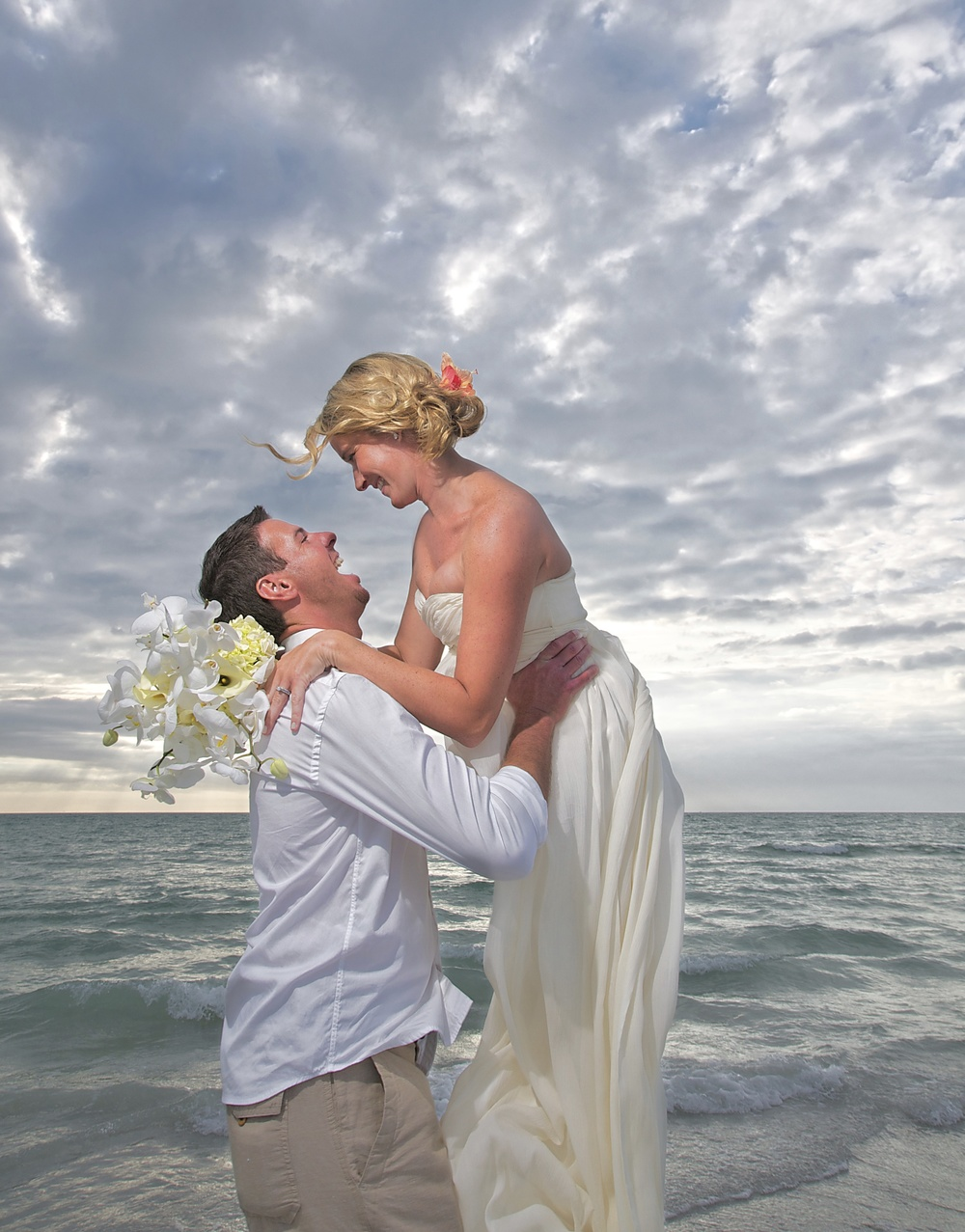 candid-beach-wedding-florida-lifting-bride.jpg