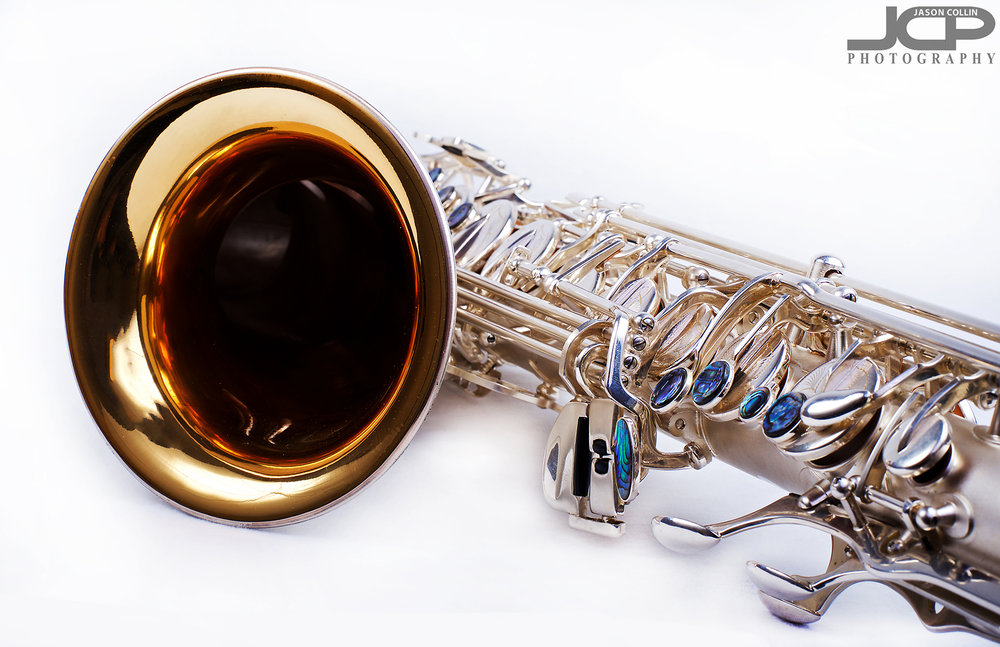 """Detailed photo of a saxophone for a client in Albuquerque New Mexico - Nikon D750 with Nikkor 50mm f/1.8G lens @ f/16 1/200th ISO 100 - Strobist: Westcott Strobe Light Plus in 55"""" octagon gridded soft box main with two 43"""" shoot through umbrellas with speedlights on the white muslin background"""