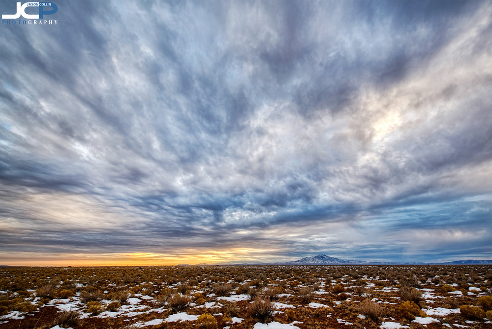Snow patches under a dramatic winter sky in rural Belen, New Mexico