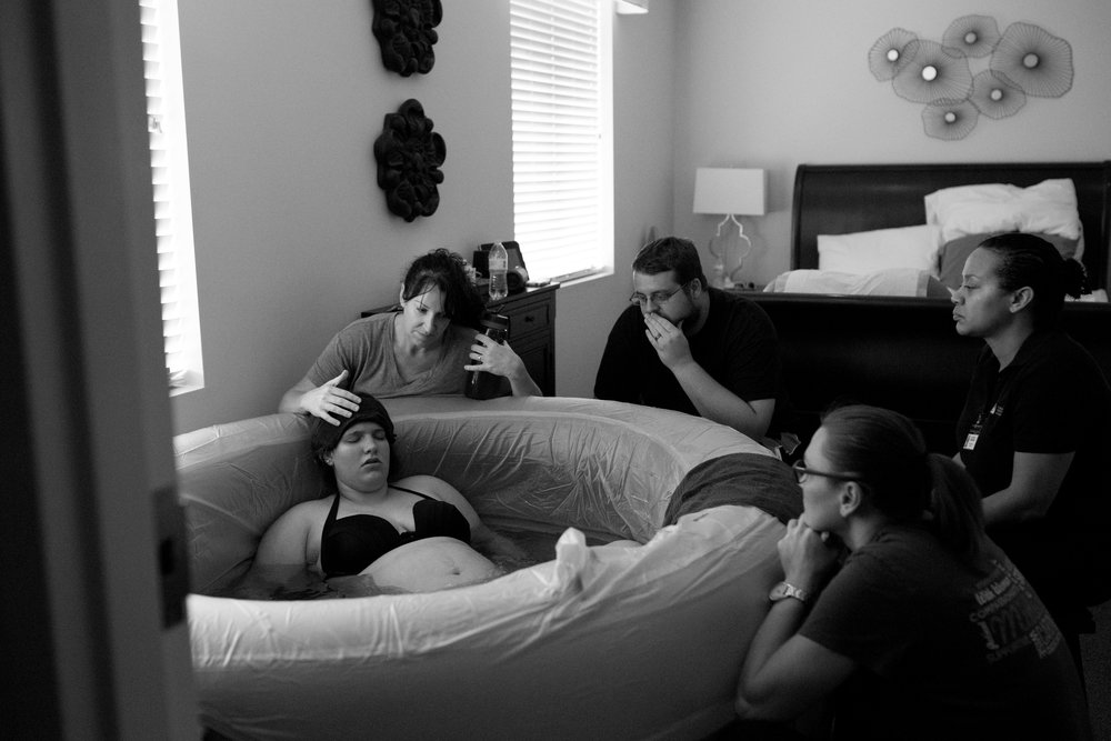 """This one has to be my second favorite picture ever. This was during transition labor. The toughest part. This moment was like an out of body experience for me. I felt like I was sitting right there beside my support system and watching myself give birth. Such a weird feeling! I look back at this picture and am amazed and honored to have felt so much love and support during that time."" - Miranda Atkins"