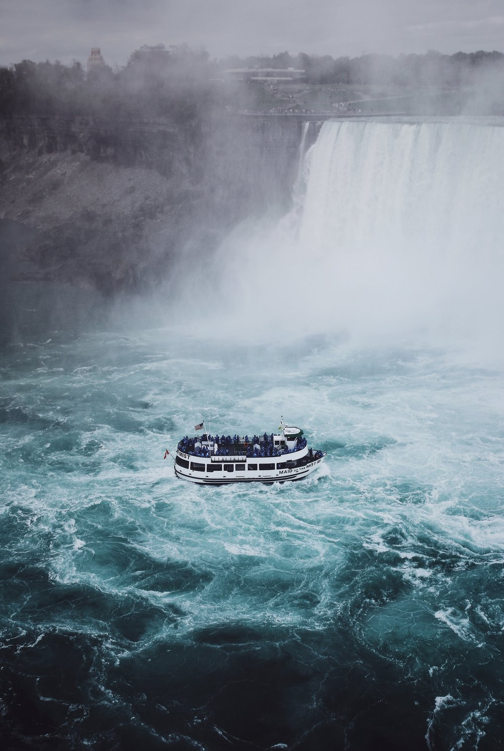 "People always ask me if I lived ""right in the Falls"". Yes. Yes I did. Like this... If you look close enough, you can see me in a towel after I showered from the mist, brushing my teeth all the while tourists invade my home in plastic ponchos.  Photo by Renan Kamikoga on Unsplash"