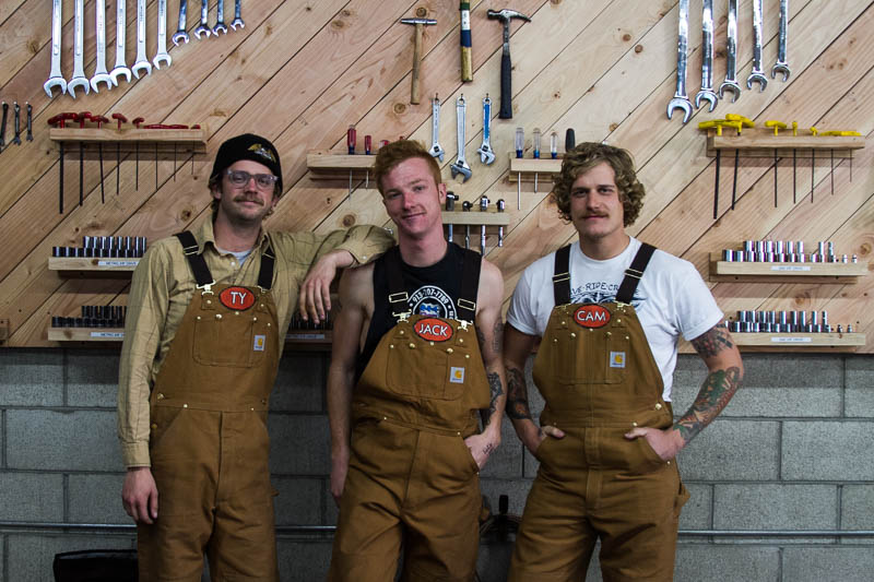 Ty, Jack, and Cam in the shop, for the Babes Ride Out profile.
