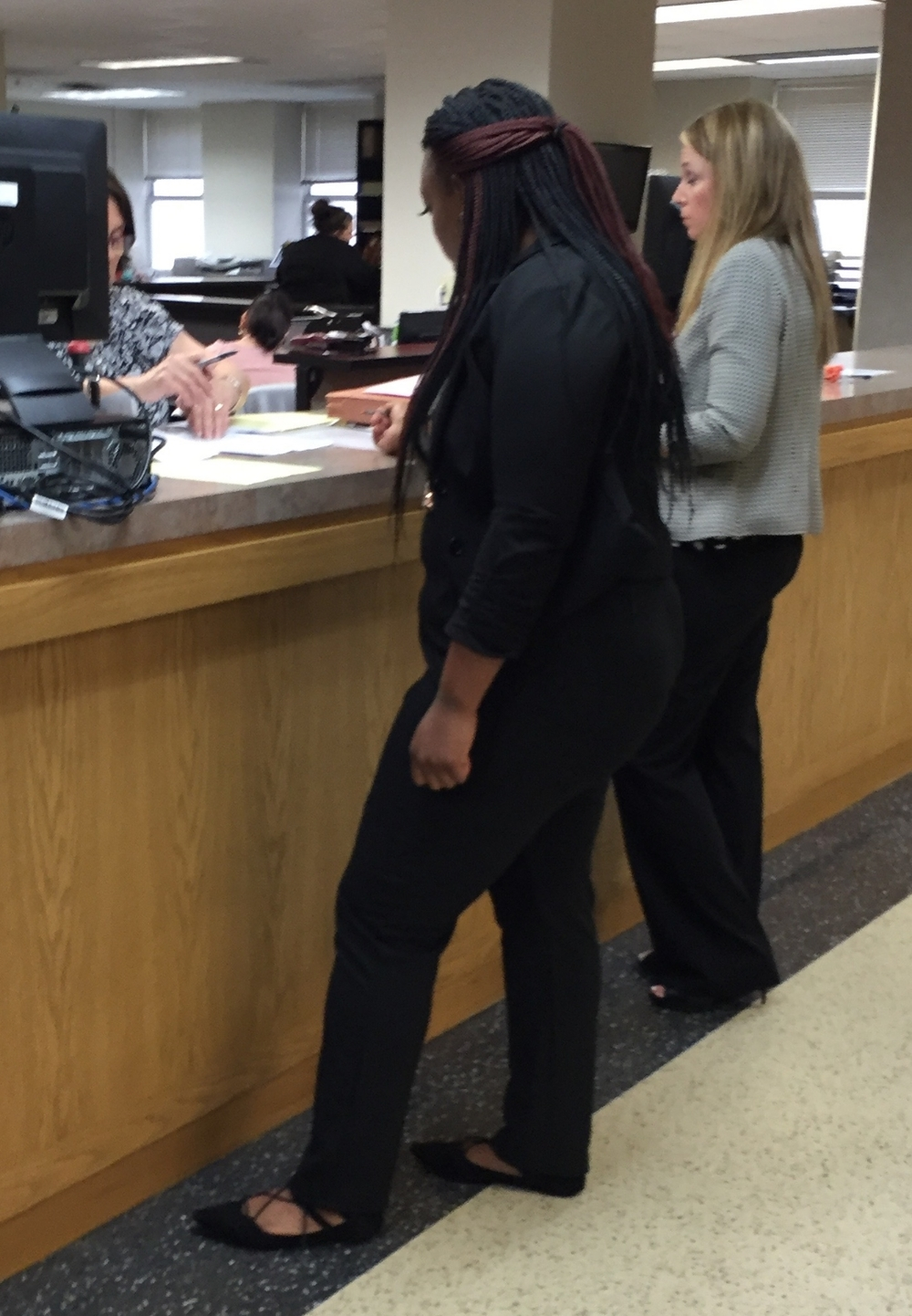 Hill at the court clerk's counter being told she has to pay all the court costs.
