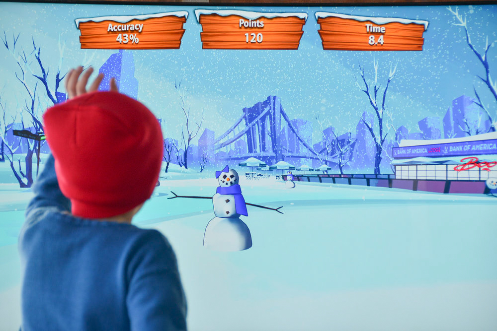 Child with red beanie in front of screen playing the motion-based Bank of America: Snowman Showdown game