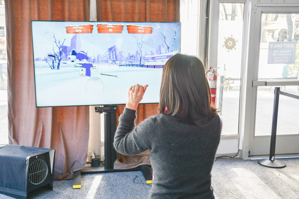 Woman playing motion-controlled Bank of America: Snowman Showdown game