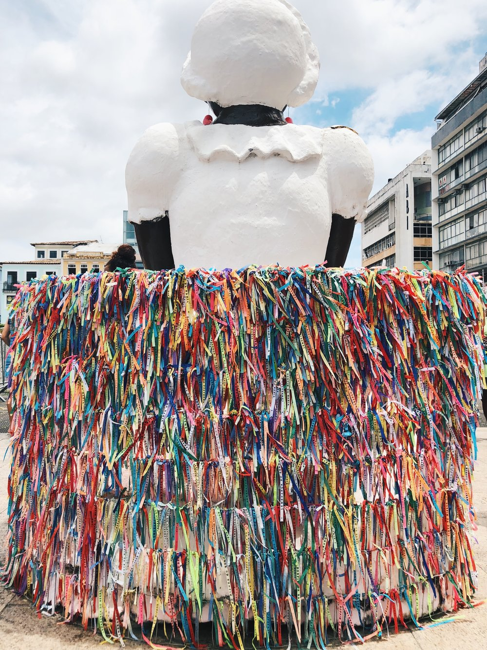 Statue of a Baiana with a skirt made of the traditional Fita de Bonfim, which  symbolizes faith and good luck.