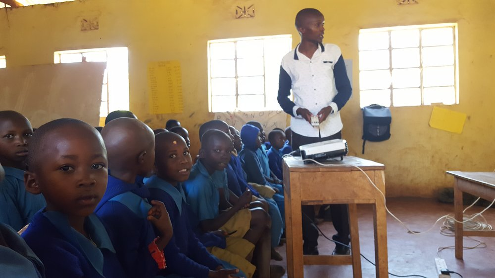 A community health worker teaches schoolchildren the importance of drinking only treated water. Teaching, however, hasn't been enough to change their habits.