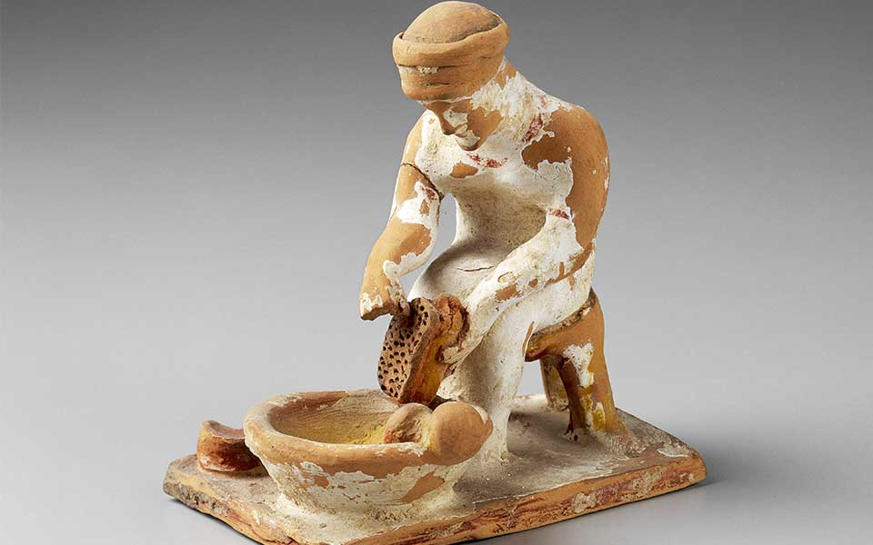 """Preparing the Kykeon: A woman grates cheese, perhaps for the """"kykeon"""" potion described in Homer; terracotta, with red, yellow and white paint; Tanagra, Boeotia; early 5th century BC (Museum of Fine Arts, Boston).    © Bridgeman Images"""