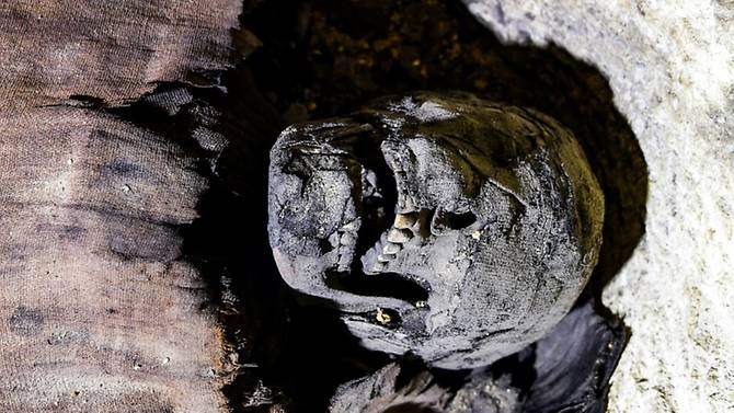 The partially-uncovered skull of a mummy found in a burial chamber dating to the Ptolemaic era (323-30 BC) at the necropolis of Tunah Al-Gabal in Egypt's southern Minya province. (Photo: AFP/Mohamed El-Shahed)