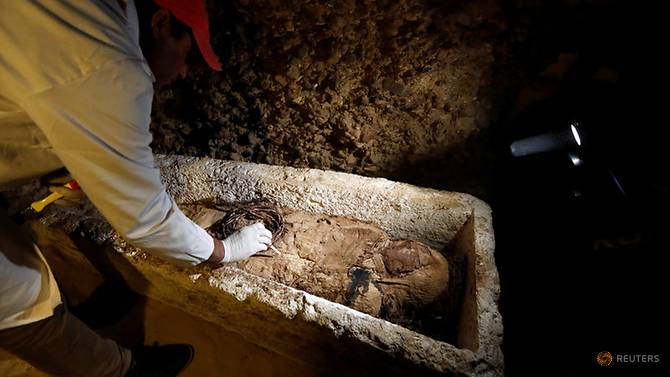 A Egyptian archaeologist examines a mummy in a coffin inside a tomb during the presentation of a new discovery at Tuna el-Gebel archaeological site in Minya Governorate, Egypt, Feb 2, 2019. (Photo: Reuters/Amr Abdallah Dalsh)