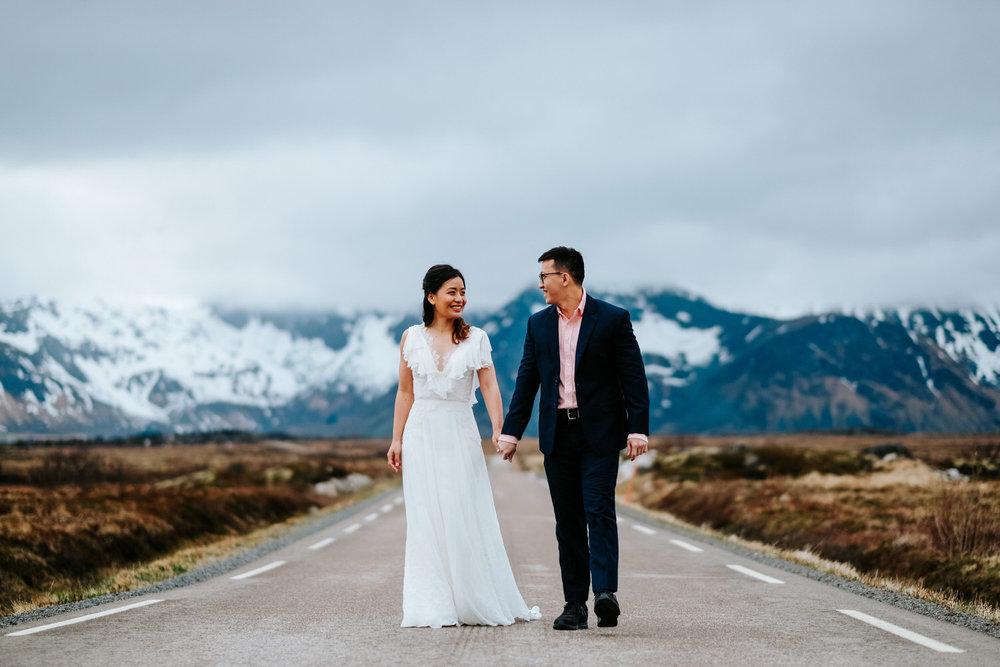 happy couple walking on road lofoten wedding