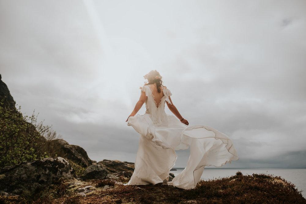 Wedding dress in wind on top of mountain in lofoten norway