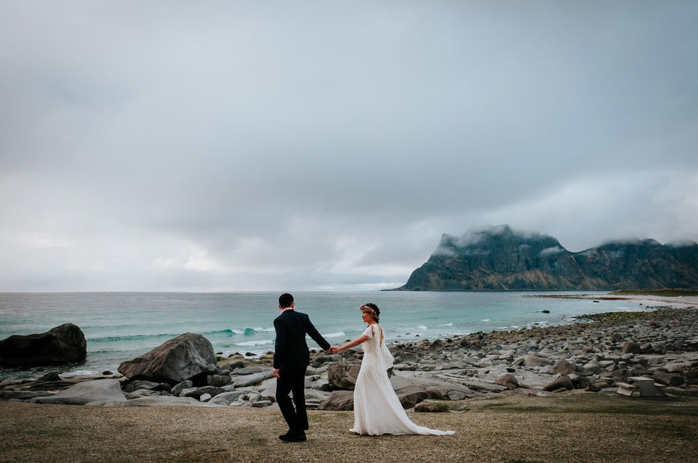 bride and groom walking in front of mountain in Lofoten