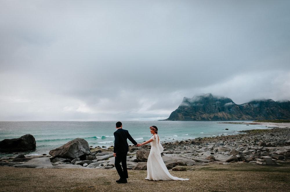 bride and groom walking in front of mountain in Lofoten