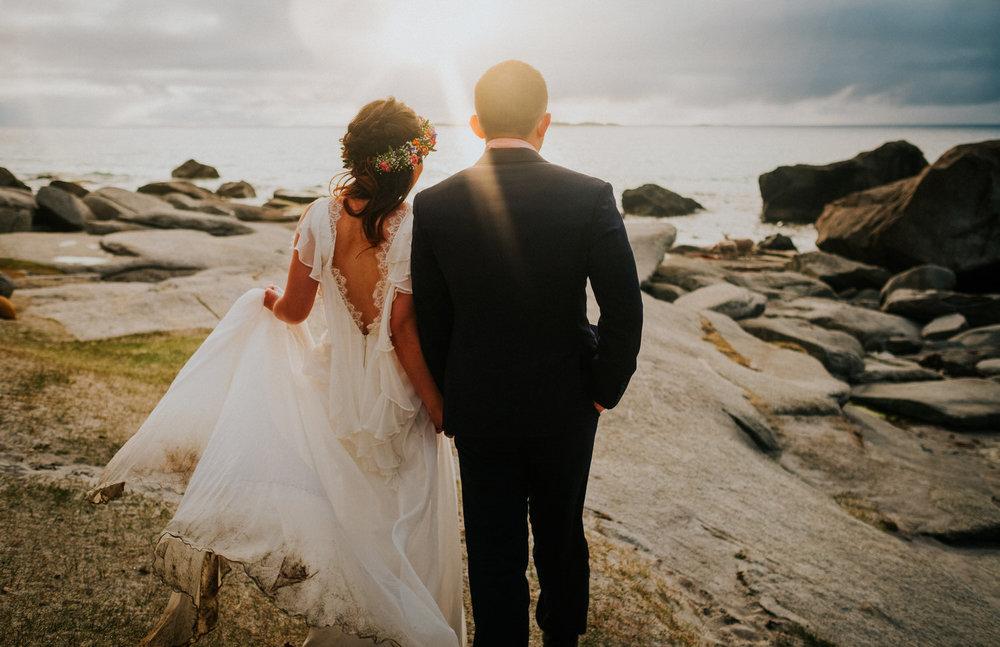 bride and groom walking into sunset on beach lofoten norway