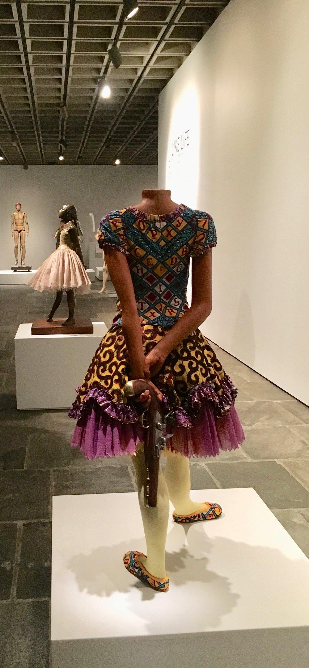 """Yinka Shonibare MBE's """"Girl Ballerina"""" (2007) stalks Edgar Degas's famous bronze """"Little Fourteen-Year-Old Dancer"""" (1881)."""