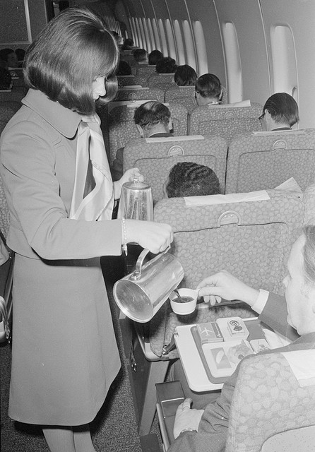Stewardess-schenkt-koffie-op-een-vlucht-naar-Rome-_-Stewardess-serves-coffee-on-a-flight-to-Rome-by-Nationaal-Archief.jpg