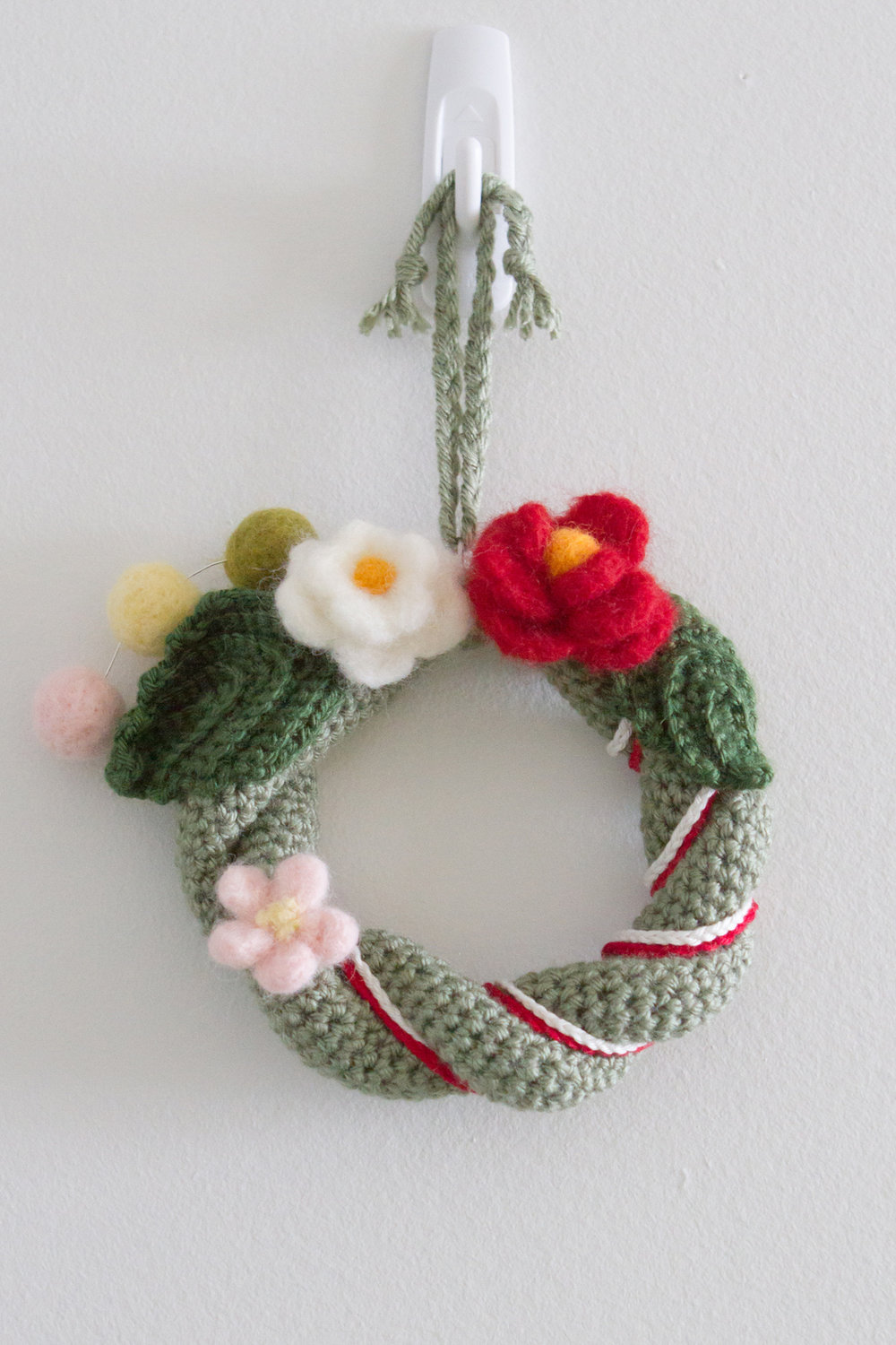 Shime-kazari. The wreath and the leaves are crocheted and the flowers are needle felted. Red and white are an important colour combo for celebrations in Japan.